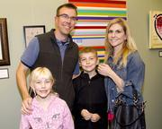 State Farm Insurance public affairs officer  Vince Wetzel poses with his wife Kristen and children Jackson and Natalie at an art exhibition at Capital Public Radio.