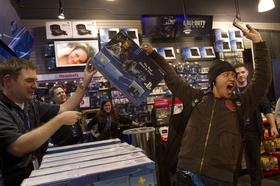 Nicholas Swe, right, reacts after purchasing the Sony PlayStation 4 console during its midnight launch event in San Francisco, California, U.S., on Thursday, Nov. 14, 2013.
