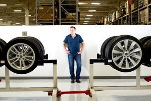 CEO Elon Musk stands with Model S sedan wheels at Tesla's plant in Fremont.