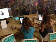 Children play with tablets set up for Sktchy.com, a social networking app that allows people to post their pictures and have others sketch them.