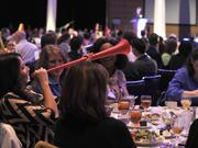 An event attendee cheers on the winners with one of the many noise makers at the 2013 Best Places to Work awards.