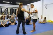 Egan Inoue talks with a group of women about self-defense techniques and demonstrates with trainer Corrie Agon during a workshop at the new Egan's Fit Body Boot Camp training center in Pucks Alley in Honolulu. Proceeds from the workshop benefit the  Kapiolani Medical Center Women & Children.