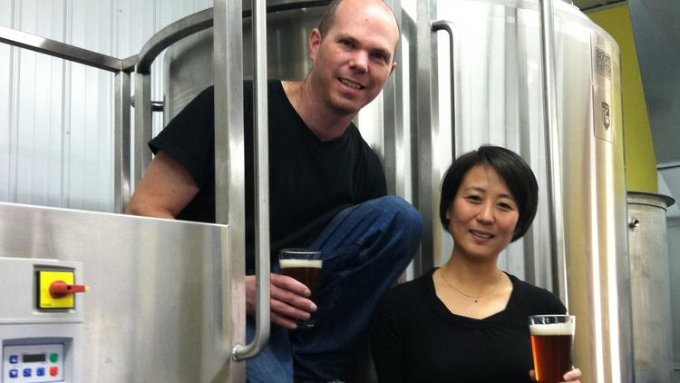Kevin and Qiuxia Welch stand in their new brewery in Minneapolis. Boom Island Brewing Co. is doubling production and adding a taproom. The couple has used SCORE to help them navigate the growth of their business.