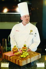 Levy Restaurants executive chef Adam Holt talks about new items. Before Holt are a West End Burger and a 16th Street Burger, offered for sale by Bridges Burger Co. to patrons in the Pittsburgh Baseball Club Level seating area.