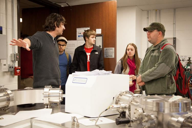 Thomas Lapen explains the function of a multiple collector inductively coupled plasma mass spectrometer housed in UH's Department of Earth and Atmospheric Sciences to a group of visiting students.