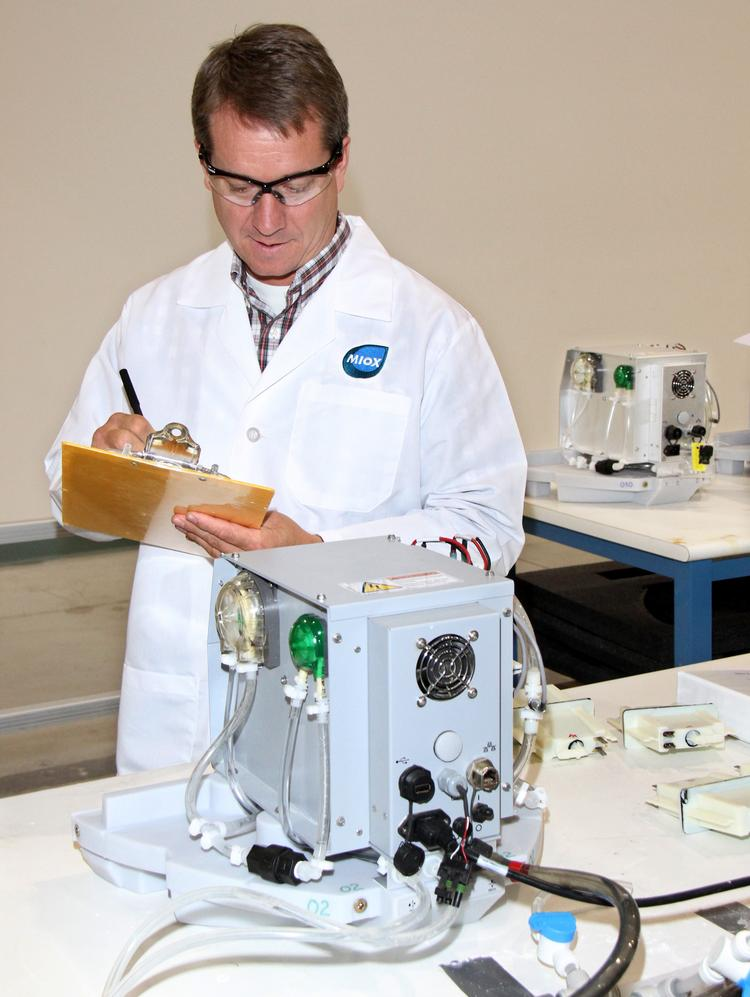 Larry Lemasters, director of operations and service at MIOX, with MIOX's Rio Zuni compact chemical generator, which the company is using in its work with the dairy industry.