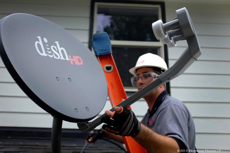 Justin Preziosi, field service specialist for Dish Network Corp., installs a satellite television system at a residence in Denver on Aug. 6, 2013.