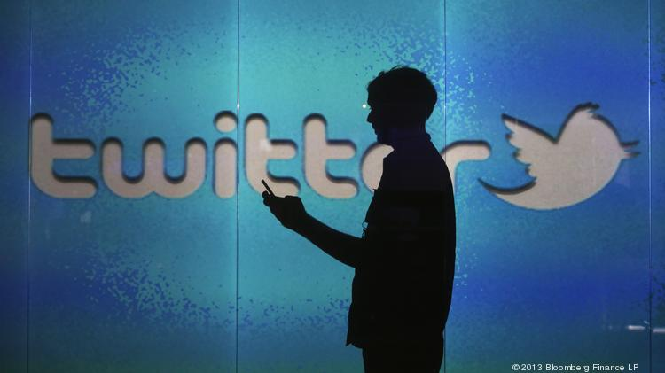 A user checks a Twitter feed on a smartphone in this arranged photograph.