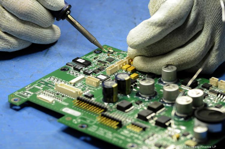 An employee works on a circuit board at Jabil Circuit Inc.'s facility in St. Petersburg. Photographer: Jim Stem/Bloomberg