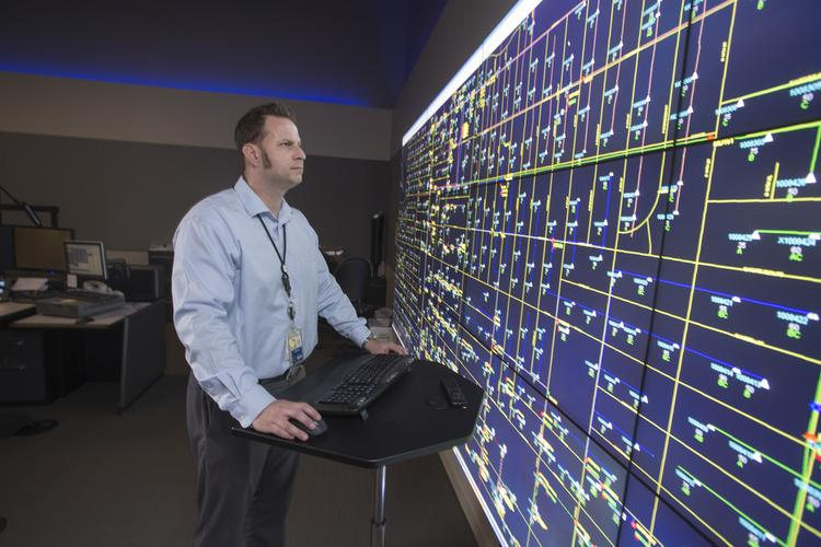 Drew Tranberg, section leader for distribution operations at Arizona Public Service Co., monitors the Phoenix-area electric grid from a large workstation. APS is adopting new technologies to help it distribute energy, even as some homeowners and businesses find new ways to secure power.