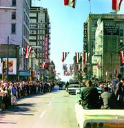 Presidential motorcade on Main Street at Griffin Street, Dallas, Texas. Photograph by Cecil Stoughton, White House, in the John F. Kennedy Presidential Library and Museum, Boston.