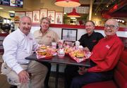 From left, Scott Redler, Bill Simon and Randy Simon are the business partners behind Freddy's Frozen Custard & Steakburgers. The restaurant is named after Freddy Simon, at right, Bill and Randy's father. The stores are filled with old family photos like the one above the table here.