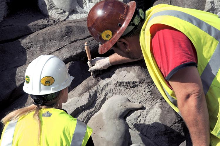 Work crews etch natural wear and texture along with penguin images into rock formations.