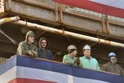 Shipyard workers look on from a lofty perch as Secretary of Defense Chuck Hagel addresses shipyard workers and sailors in a speech in front of the USS Zumwalt, DDG-1000, at Bath Iron Works.