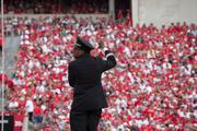 The Ohio State University Marching Band provides the soundtrack of the game, filling in what can be interminable TV timeouts with music. For band directors like Mike Smith, that can be mean a balancing act - literally - as they try to keep one eye on the field while also keeping the band in time, standing on a stepladder.