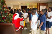 Santa Claus hands out books donated by Houghton Mifflin Harcourt.