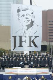 Dallas Mayor Mike Rawlings spoke in front of a huge JFK banner and the The U.S. Naval Academy Men's Glee Club.