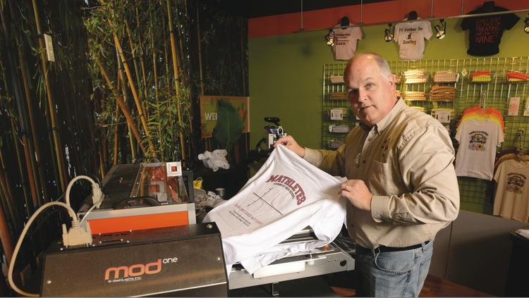 Kevin Mendel, franchisee of a Big Frog Custom T-Shirts & More store in Bloomington, removes a custom T-shirt from a printer.