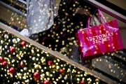 Black Friday eclipses all other days as the dominant shopping frenzy. A shopper carries a Victoria's Secret Stores LLC bag while riding an escalator at a mall in California. Photographer: Sam Hodgson/Bloomberg