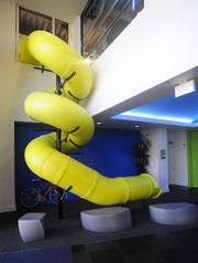 At Box HQ, a twisty tube slide provides conveyance for those who find stairs tiresome. See more photos from inside the campus here.