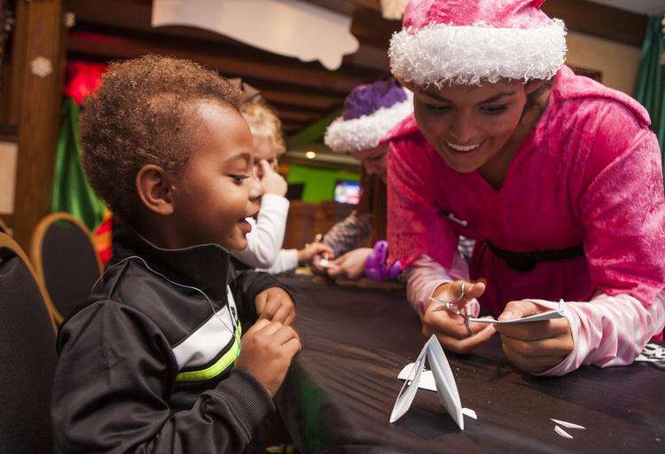 Braxton Harper, 2 years old, and his family traveled from Princeton, Ky., to experience the Galt House Hotel's Christmas attractions. He is shown making a snowflake with the help of an elf named Peppa'.
