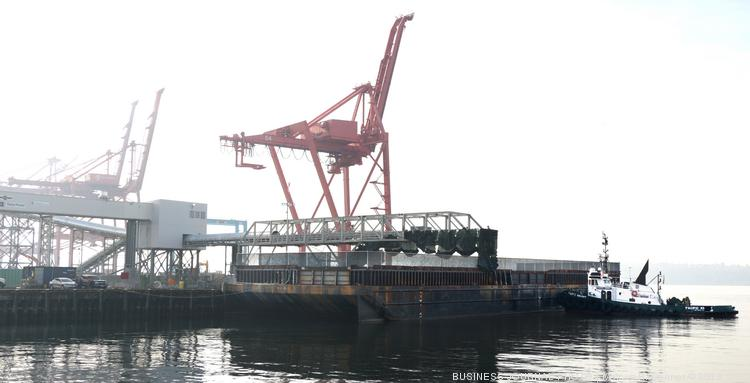 A tug tends a barge that is set to receive soil from the tunnel boring machine digging the Highway 99 tunnel under Seattle.  The soil is brought to the tug along the long white conveyer built that runs the length of the pier.