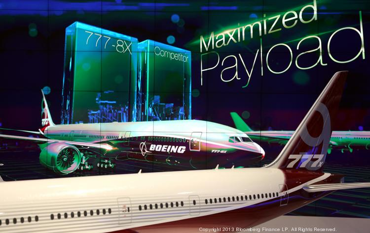 A model of Boeing's 777X aircraft, manufactured by Boeing Co., sits in front of a picture display for the new aircraft on the company's stand during the 13th Dubai Airshow at Dubai World Central (DWC) in Dubai, United Arab Emirates, on Monday, Nov. 18, 2013. The 13th edition of the biennial 2013 Dubai Airshow, the Middle East's leading aerospace event organized by F&E Aerospace. Photographer: Duncan Chard/Bloomberg