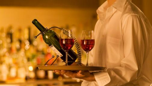 Waiter carrying wine to a table