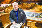 John Russo Sr.'s train set, which features two waterfalls that use 95 gallons of water when working, wouldn't fit around a regular-sized Christmas tree. Russo, near the elaborate control panel, said his is the second-largest train layout on the East Coast.
