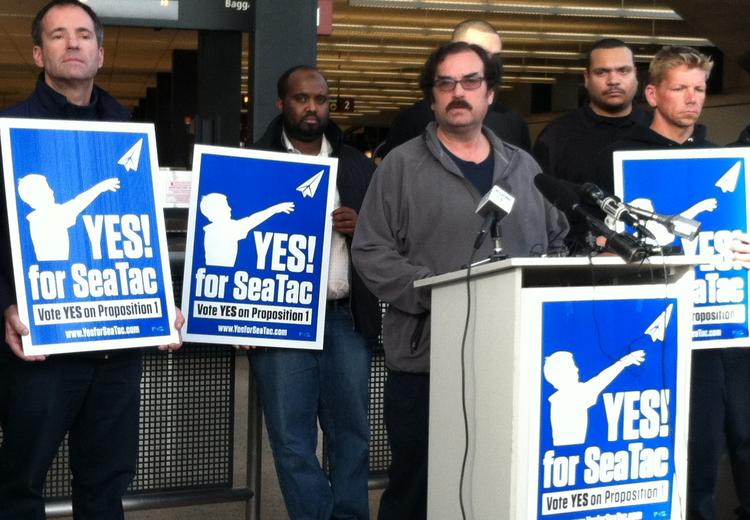 Chris Smith, at the podium, says he'll be able to quit one of his two jobs thanks to the  SeaTac minimum wage measure. He spoke at a victory rally at the airport on Nov. 24, the same day elections officials certified the measure's passage.