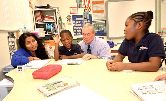 Jonathan K. Hage visits Lidia Han's first-grade class at North Broward Academy of Excellence, working with students Marlon Alezy and Zharianne Wharton.