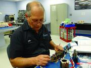 A Genesis Aviation employee works on a component.
