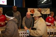 Bobcats head coach Steve Clifford (center) helps families choose canned foods for their Thanksgiving dinners. Also pictured is Rod Higgins (left), president of basketball operations.