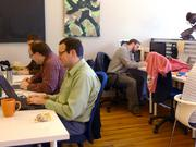 Cube members, including co-founder David Hewitt (far right), keep busy on a Friday afternoon.