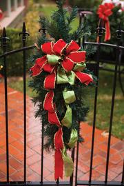 Garland and ribbons hang from the front gate leading into the yard.