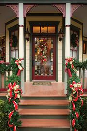 The front door leading into the home of Dr. Stephanie Russell is full of greenery, lights and red and gold ribbon.
