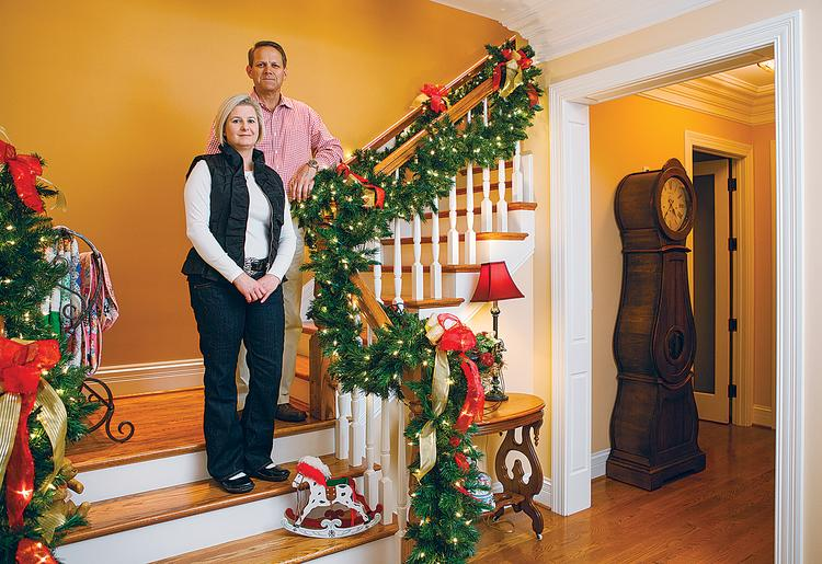Dr. Stephanie Russell stands on the front stairwell of her home with Rick Crabtree, her significant other.