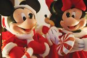 Christmas themed Mickey and Minnie Mouse figures sit on a dresser.