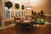 The breakfast room is decorated with three wreaths along the windows, holiday place settings and a nativity scene.