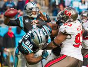 Panthers quarterback Cam Newton looks for a receiver as Jonathan Stewart blocks defensive tackle Gerald McCoy.