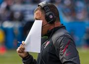 Tampa Bay head coach Greg Schiano hides his face as he talks to his staff on the headset.