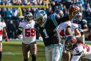 Panthers quarterback Cam Newton evades tacklers on a long gain after a scramble.