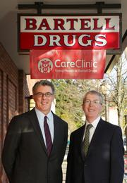 """From left, Scott Armstrong, president and CEO of Group Health Cooperative, and George Bartell, chairman and CEO of Bartell Drugs, announce their companies will work together to create retail clinics inside Bartell Drugs locations, called """"CareClinic: Group Health at Bartell Drugs."""" One of the clinics to open next year will be located at the Bartell store in Seattle's University Village, pictured here."""