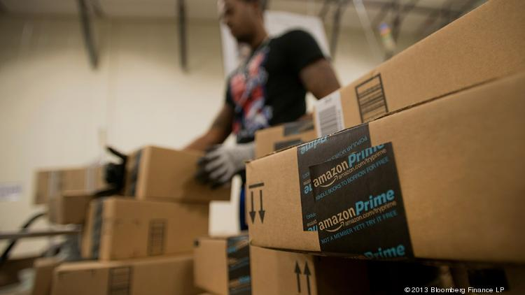 An employee stacks items to be shipped at the Amazon.com Inc. fulfillment center in Phoenix, Arizona. Sources indicate the company is scouting to put such a facility in the Pittsburgh area. Photographer: David Paul Morris/Bloomberg