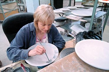 Michelle Cox painted a flowered border on a Louisville Stoneware plate. The pottery company saw big sales over the weekend.