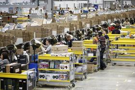 Employees package customer orders ahead of shipping at Amazon's Rugeley, U.K. facility.