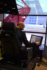 A convention guest tests out a crane simulator. Even construction workers need cost effective training.