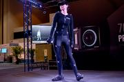 """A test subject demonstrates the Opti Track motion capture system. I'd feel a little weird in that costume, too, but the animated """"mini me"""" in the background makes it worth the experience."""