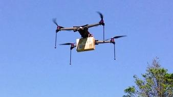 An image of an unmanned aerial vehicle carrying a package.