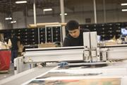 An employee cuts poster sized prints with a big cutting tool.